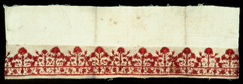 pillow border of fine tan canvas embroidered with a design of conventionalized flowers (pinks) in satin, feather and chain stitch in red silk; the border is in two sections, the lower serving as a narrow border to the upper, the whole of which is sewed to a wider strip of coarse canvas