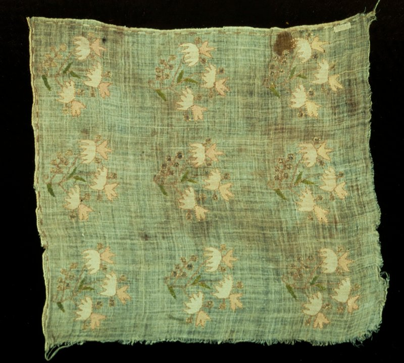 fragment of loosely woven linen, probably a towel end, embroidered in three rows of floral sprays containing three units each, cream, rose, blue and tinsel threads; three sides have a narrow border of tan and green stitching; silk on linen