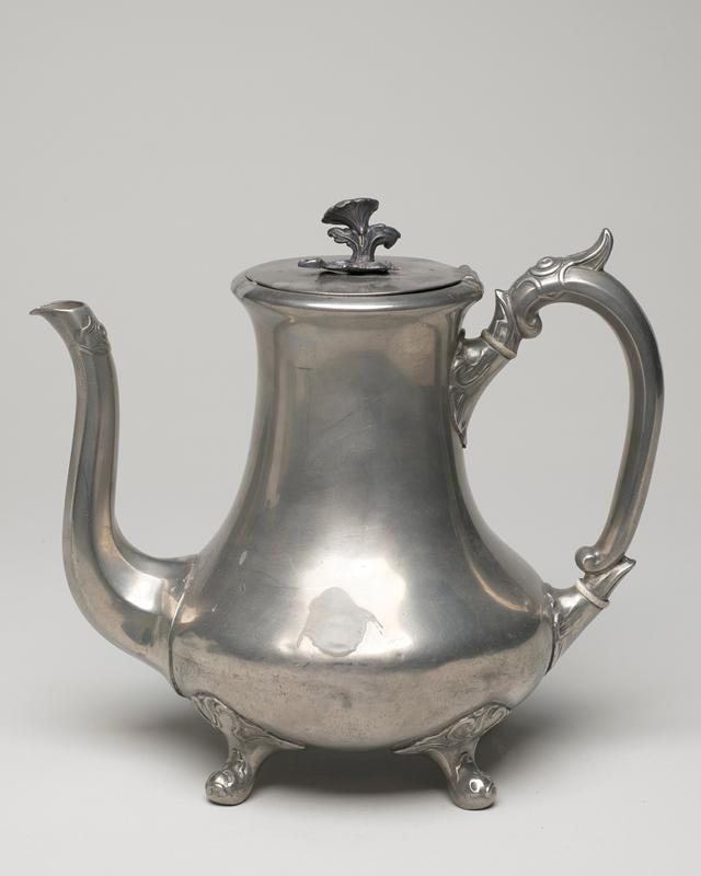 Teapot, white metal, cat. card dims H 8-1/4' With elongated bell-shaped body mounted on four pad feet attached to body with leaf forms. Long, flaring spout joins body at base, shaped handle decorated with leaf forms, cover with flower finial and applied leaves.