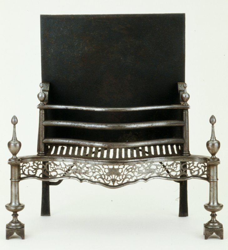 dog grate, the apron is pierced in a design of vines and salamanders; baluster-shaped firedogs support the basket, which has bowed bars of steel across the front, and baluster-shaped columns at each corner