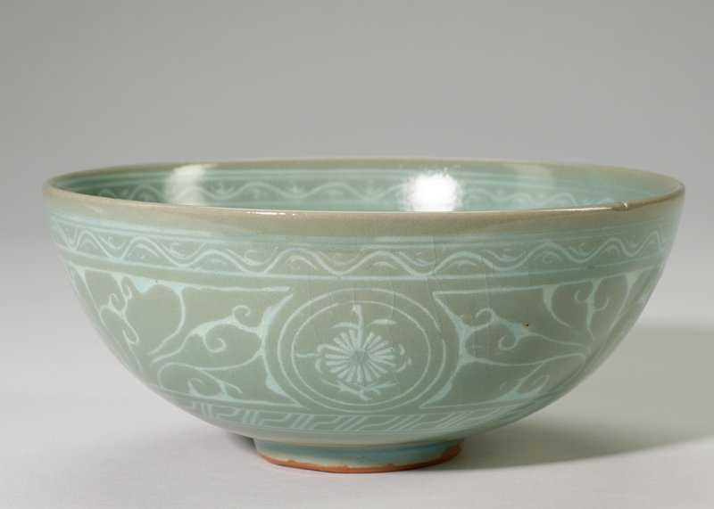 Bowl, Celadon ware, soft gray green glaze decorated inside with medallion surrounded by three others. Three medallions on the outside.