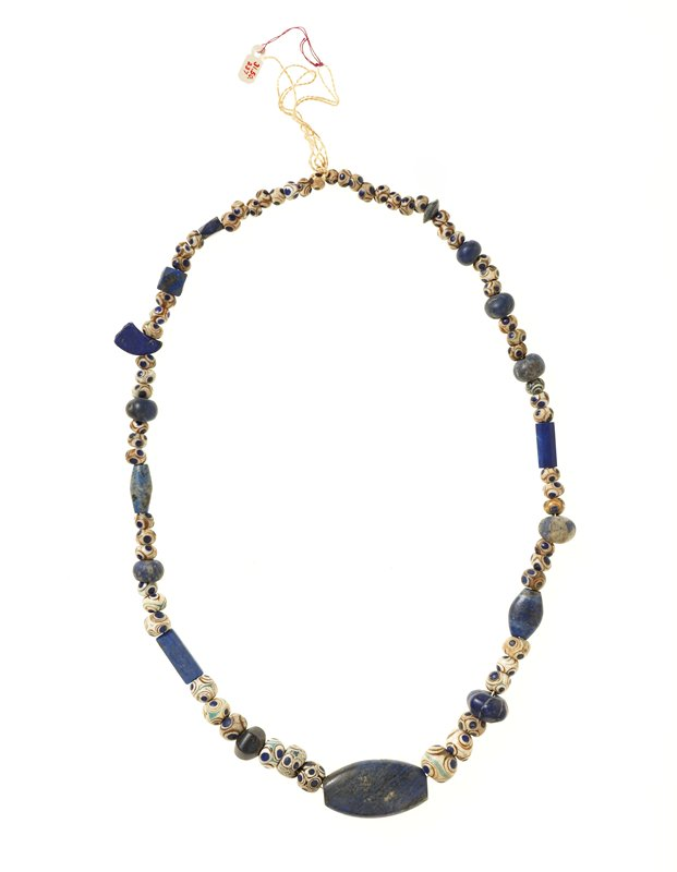 Necklace, beads (medium?), Egyptian; large bead L. 1-3/8' W. 3/4'; unnumbered Necklace of 64 patterened beads interspersed with lapis lazuli and other beads; large flattened lapis lazuli bead at the center.