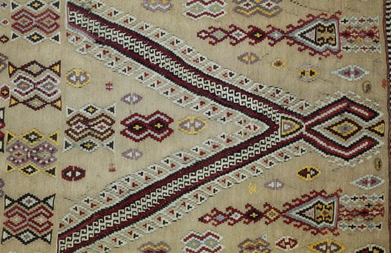 Rug, small, Khilim in pale green. Prayer design in red. The field contains various unrelated geometrical forms in various colors. Side and end borders of different widths and design. Side borders have a considerable amount of black. Finely woven.