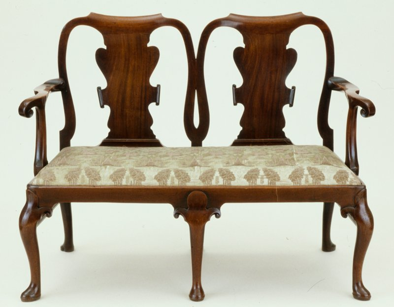 settee, Queen Anne style, with club feet on the six legs of attenuated cabriole shape; the knees are carved in ther outline of a leaf which terminates in a simple scroll to frame the ear; on the central front leg the curve of the knee is negligible and the leaf is seen in its complete frrom; the back is formed of two hooped chair backs with solid vase shaped splats; the simple curved arms are unadorned; modern green and gold damask upholster