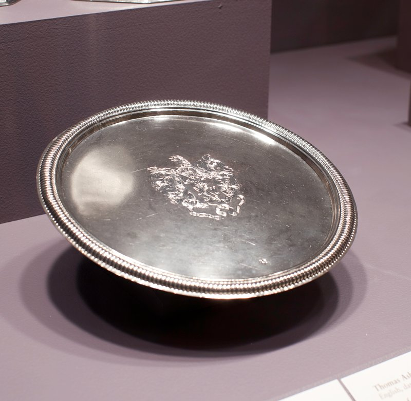 footed salver with gadrooned rim and foot; engraved Dudley coat-of-arms; fleur-de-lis mark with circle in a heart on top beneath coat-of-arms; mark rare after 1705, so paten probably dates before that time