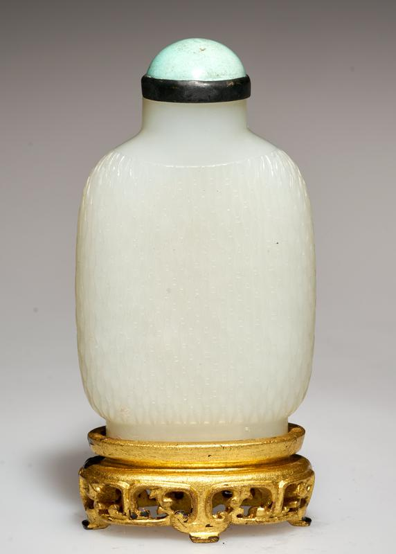 Snuff bottle, white jade carved with a broad band in tear drop design. Turquoise top; gold stand.