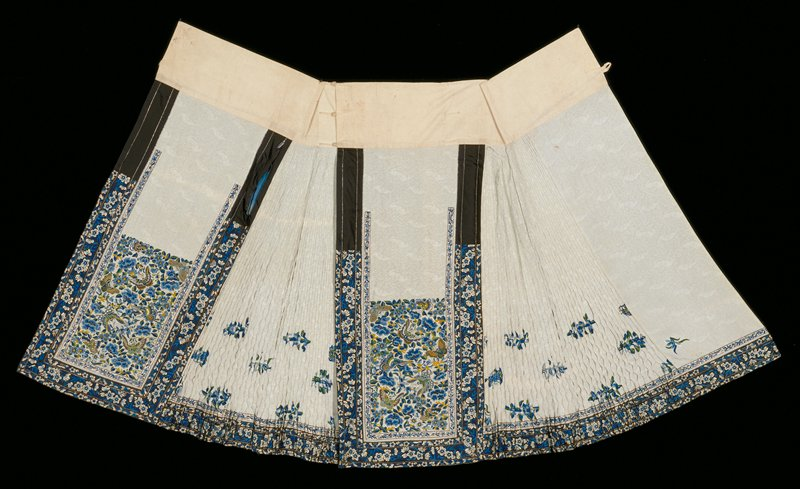 Skirt, pale blue self-toned brocade in two sections, each divided into three panels, one plain, one pleated and smocked with blue flower sprays at bottom, and one heavily embroidered with floral sprays and butterflies. This panel partly enclosed by narrow white satin band embroidered in blue flowers and piped with silver tissue, also by wide band of black satin (in three widths) embroidered in white and three shades of blue. Three pipings of silver braid. All embroidery in twisted silk, long and short satin stitch. Broad cotton waistband in two sections, cotton loops and buttons, Lined with old blue silk except for pleated panels which are unlined.