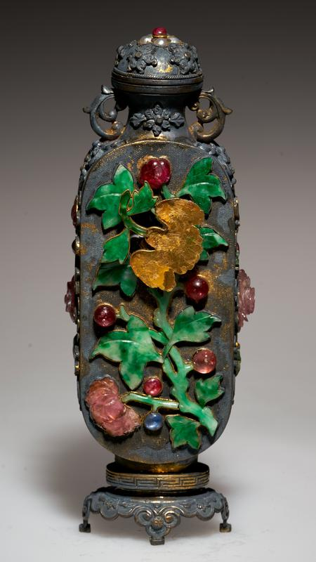 Snuff bottle (one of pair 36.5.2-3), gold inlaid on two flat sides with a large floral spray of semi-precious stones Smaller floral designs in semi-precious stones on narrow sides. Two handles formed of gold scrolls. Gilt stand.