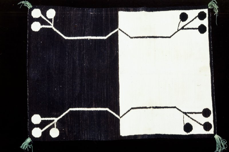 "saddle blanket, Hopi, so-called ""Divorce"" blanket with one half of the field in white and the other half in black; in the outer corners of the two fields, white on black and black on white, a bent stem terminating in three solid discs; edges overcast, corners finished with tassels of green and black wool"