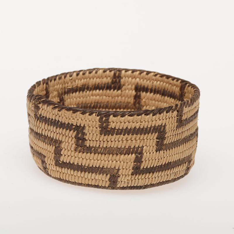 miniature basket, shallow and vertical-walled; finely coiled; design is a stepped, linear pattern in natural and black, which completely fills the side walls
