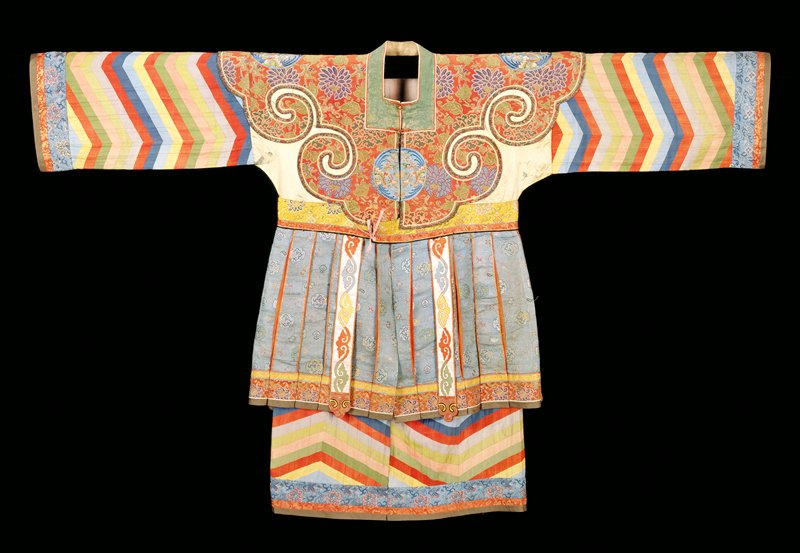 Actor's robe, upper section made of pieces of old floral brocades in red and yellow, applied on a yellow satin ground. Skirt of accordion pleated pink silk entirely concealed by over-skirt of strips of blue and gold brocade. Sleeves and skirt border made up of slanting strips of colored silk bordered by bands of the brocades. Embroidered medallions of blue satin. Two embroidered tabs back and front. Square neck. Lining of pink silk and cotton.