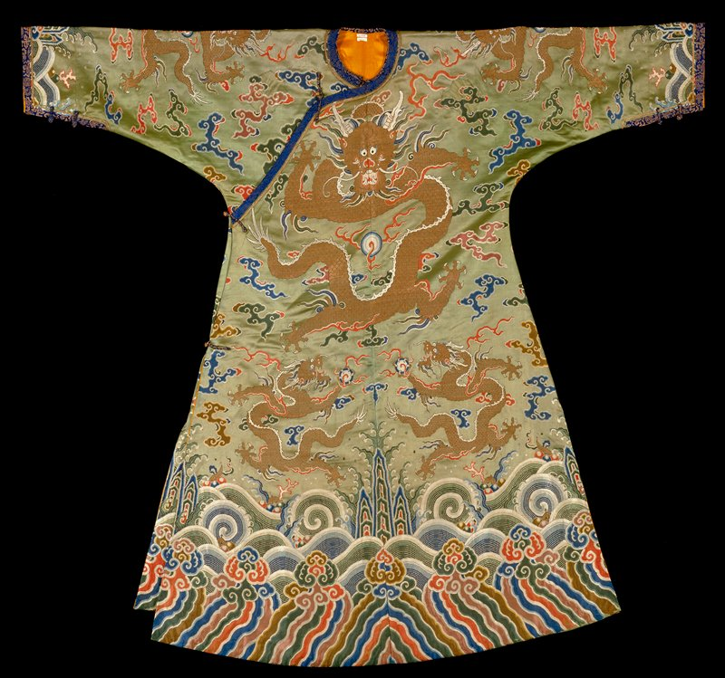 Imperial concubine robe of rich green brocade. The sleeves have been altered to fit the wearer. Shades of blue, green, red, rose and yellow on green satin ground. Dragons in gold. Note use of imperial five-clawed dragon.