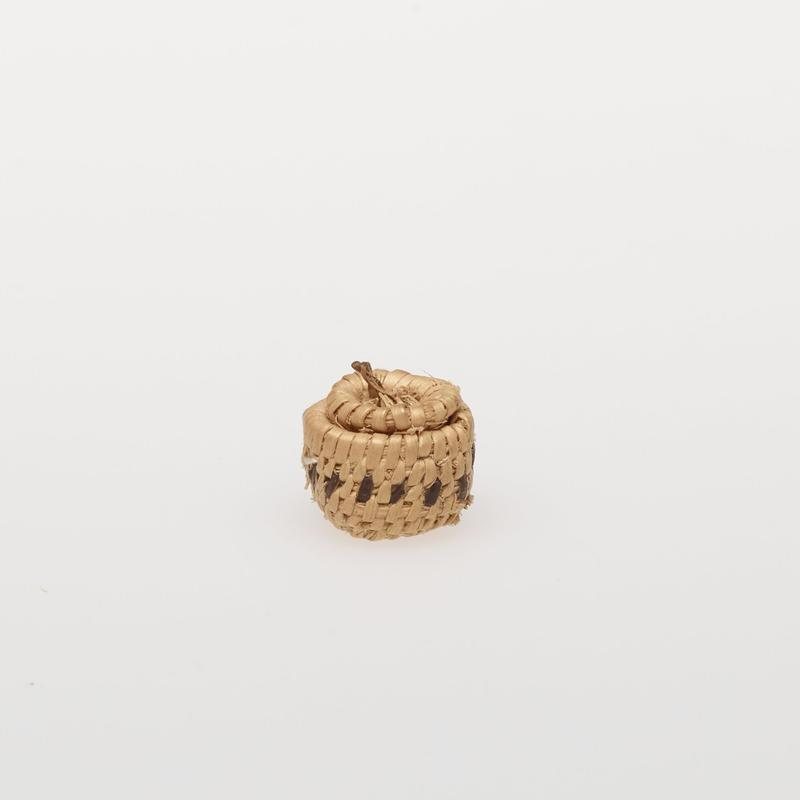 Minute round basket with cover; coiled. Design consists of a band of dots. Colors are natural and black.