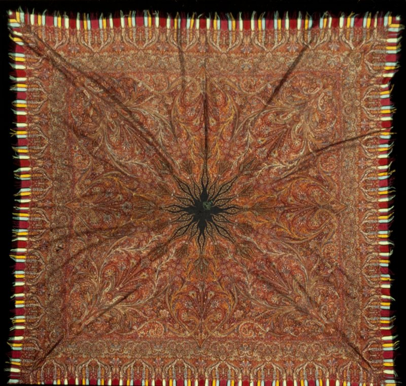 Kussaba, or square shawl. Elaborate all-over design of floral arabesques and trailing vines in shade of red, green, yellow, and blue. Black center with embroidered cartouche. Border of flowering shrub, blossoms, arabesques, with supplementary border of strips of fringed wool of various colors. An exceptionally fine example of weaving, with two sides almost identical in appearance. Several holes and tears appear in border. Cf. 30.62.4 which Mrs. Bovet thinks is the same and possibly woven by the same hand. 42.48 purchased in Pasadena; 30.62.4 at Liberty's