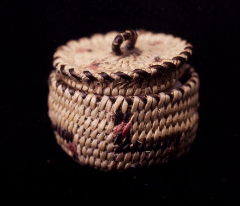 Miniature round basket; coiled. Design consists of a stepped radial pattern in red and black. Colors are natural black and red.