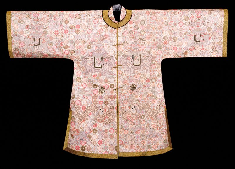 Coat with solid needlepoint ground of all-over lozenge and swastika design in pale shades of pink, grey, tan, green and peach. In lower area appear dragons and chilin; in the upper area and on sleeves appear elephants, and between are phoenix. The long-life characters in the field, as well as the blankets of the elephants,are embroidered in peacock feathers. Cuffs, collar, and edged are bordered with gold and black brocade. Standing collar of the needlepoint. Lining of soft blue satin damask with large floral pattern. Note Mrs. Harris says this robe is reputed to have been worn by the Empress while bearing a child as all the symbols are thought to bring good luck.