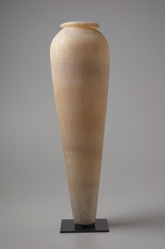 tall, conical shaped vessel with slightly inward-turning shoulder and outward-flaring lip rim; white alabaster; black metal mount