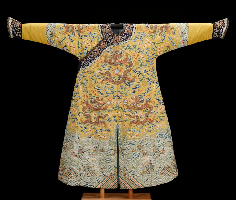 Emperor's ceremonial twelve-symbol coat of yellow k'ossu with nine five-clawed dragons, those in profile clasping the Heavenly Jewel. Background of loosely drawn cloud forms, bats, and good luck emblems in shades of blue, green, violet, red, rose, and gold. At bottom wide border of tossing waves dotted with flowers, flower vases, swastika and other emblems. At sides, center front and back where coat is slit, small areas of slanting, wavy stripes. Similar reduced border at elbows, where sleeve is extended by a strip of ribbed yellow silk finished with cuffs of dark blue k'ossu. Band of same dark blue k'ossu around neck and down front to under arm. Coat lined with figured blue silk and lightly interlined. Yellow ceremonial coats worn in sacrifices to earth.