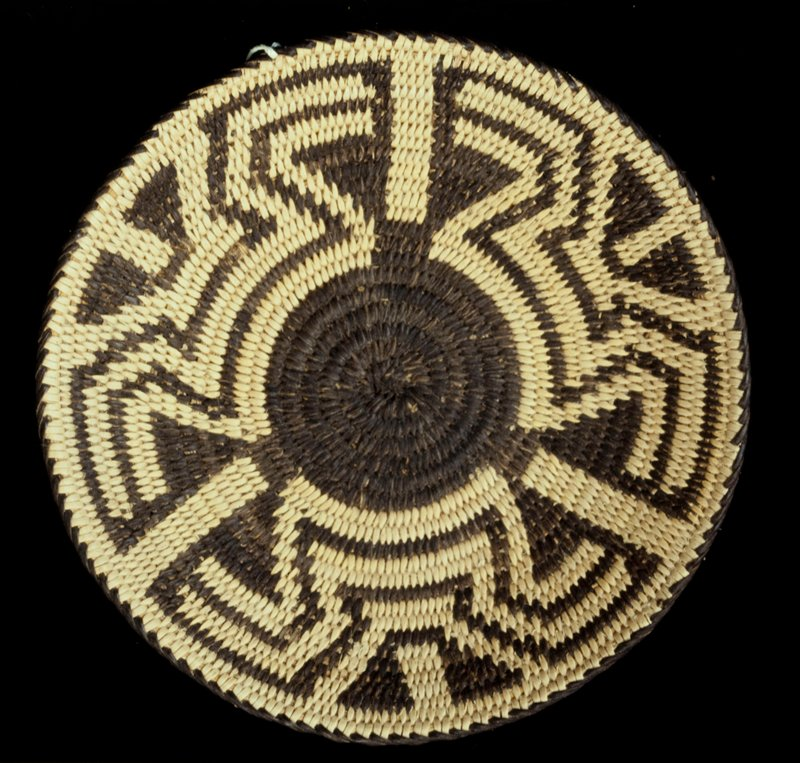 Small plaque with slightly flared edges; coiled. Design consists of a central devil's claw surrounded by modified fretwork (possibly butterfly-wings). Colors are natural and black.