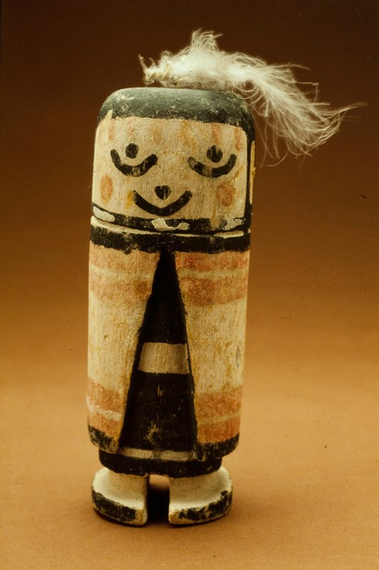 Hopi ceremonial doll, wood, painted; face white, back and sides of head black; head emerges direct from shoulders; chicken feather serves as top-knot; cloak white with red stripes, garment underneath black and white belt; twentieth century