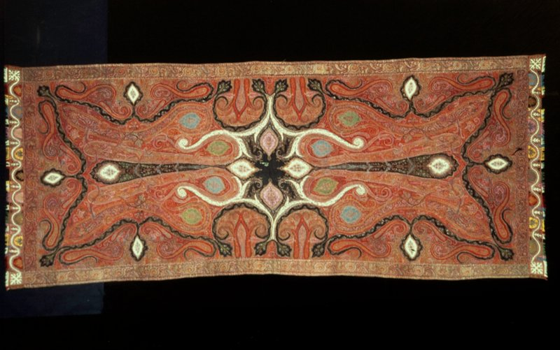Long shawl, of hand-loom woven patchwork with a design of inserted floral medallions in shades of green, red, turquoise blue, and yellow. Field carries large cones and arabesques. Design and colors show European influence. Partially lined with black cotton. #11 in travelling exhibition.