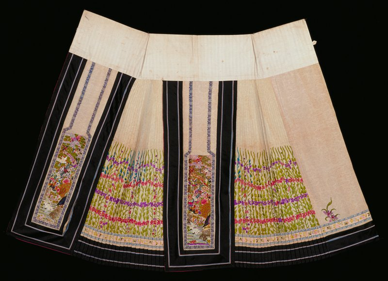 Skirt of ivory white figured silk, the side sections of tacked-down accordion pleats embroidered in the lower sections with tall sprays of flowers in cerise, purple, blue, and green. Main panels embroidered in satin stitch with a landscape design of birds, bats, flowers, mountains, and trees, in shades of blue, green, pink, cerise, yellow lanendar and orange. Main panels and bottom bordered with a wide band of black satin with pipings of light blue and grey silk. Bottom has a second inner border of white satin ribbon of floral design with blue borders. Main panels lined with thin, cerise silk.