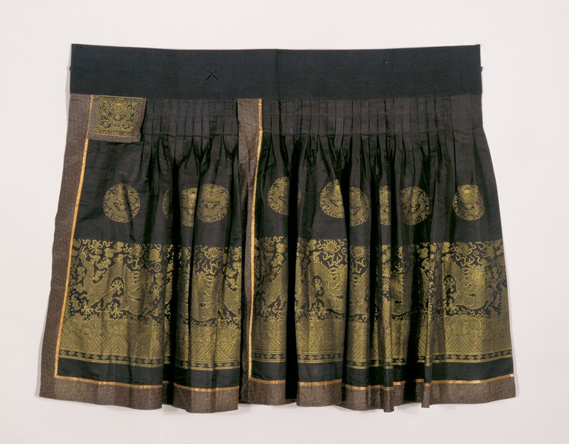 Skirt of blue-black silk with 5-clawed dragon border and medallions brocaded in chartreuse yellow. Around the bottom a band of gold and black brocade of interlocking Y pattern. The skirt is pleated with stitched box pleats below the waist band. Cf. 42.8.205,212 for similar tailoring and design.