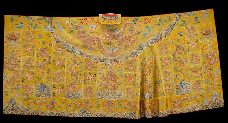 Buddhist priest robe of embroidered yellow satin with one end gored. Int he many small squares symbolical of Buddha's mendicant days, are embroidered five-clawed dragons in couched gold, and large peony blossoms with leafy tendrils in shades of red, pink, blue, and green. The gored sections contain two peony blossoms with trailing branches. In the borders and larger dragon panels appear the universe motif, with coral, swastikas, and other symbols appearing in the waves. Loosely drawn clouds. In the end sections of the upper border, bats appear. The 'patched' character of the robe is accentuated by bindings of ivory satin which mark off the various squares. Lining of pink silk. Colors are clear, and include shades of blue, green, red, pink, yellow, mauve, and brown. Atached to center of upper border a flap with embroidered canopy to shield wearer from dragon's eyes. This robe close in design to 42.8.134. Cf. dragons, clouds, and wave areas with other K'ang Hsi robes.