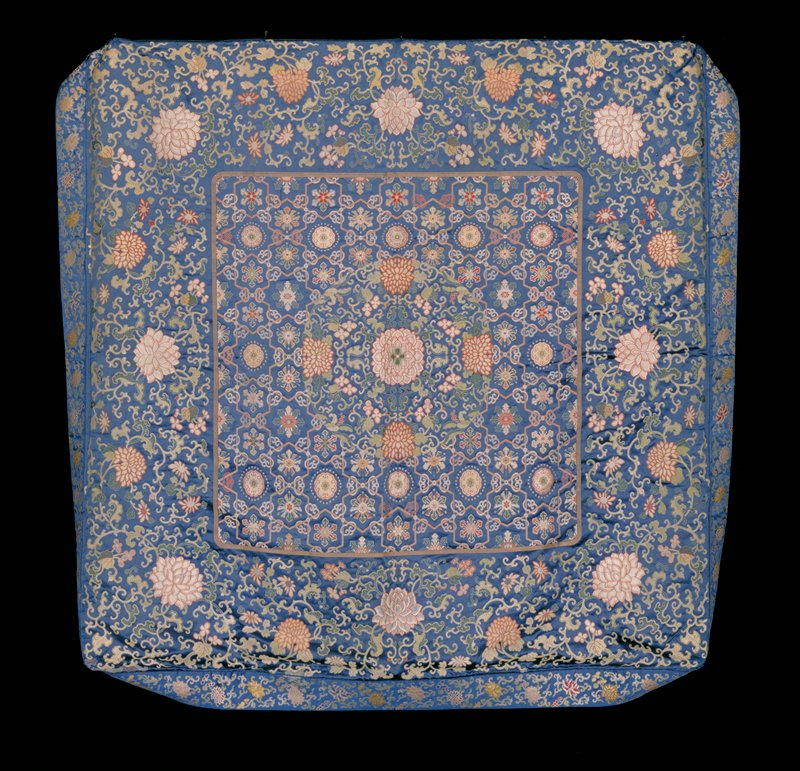 Throne seat cushion of dark blue satin brocade. Square center panel with diapered background and large floral medallion in center. Diapers encased with single tight clouds, and each contains a stylized flower or symbol. Wider border of peonies, chrysanthemums and trailing leaves.(Cf.42.8.140). Colors pinks, blues, greens, tan, yellow, mulberry. Outer narrow border of floral sprays is boxed to fit over throne cushion. Lining of Imperial yellow satin.