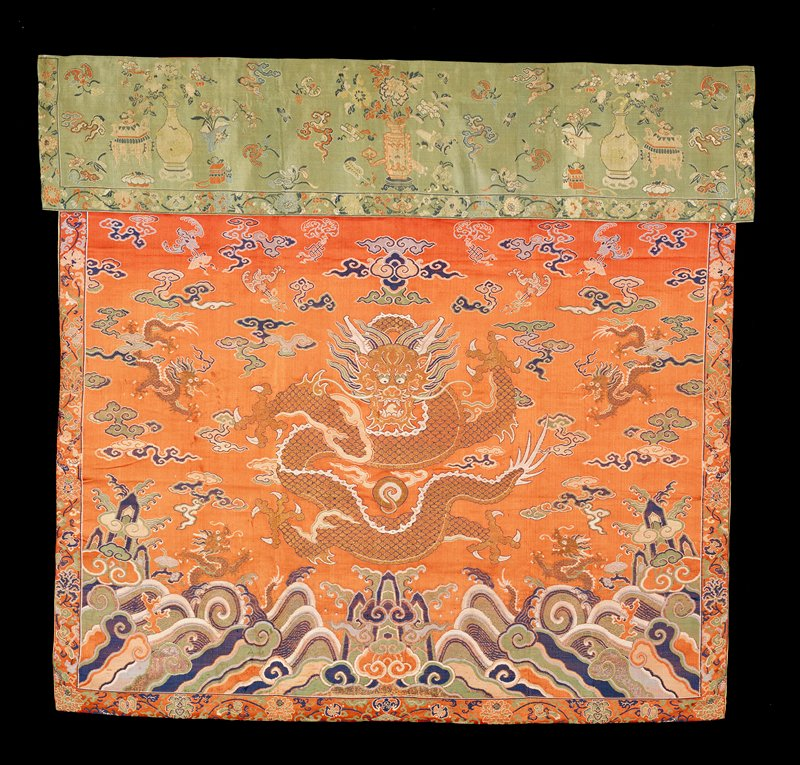 Altar Frontal of rust-red brocade. Five four-clawed dragons, one large one in center, in gold. Field of loose clouds and bats gripping symbols in shades of blue, green, pink and peach. Below, the Eternal Sea with branches of Coral in the curling waves. Border of the satin brocaded with running design of flowers, bats and symbols. Across the top a loose strip of green satin brocade with a design of bats, clouds, sacred vessels, plum blossoms, narcissus, and Taoist symbols. Border of the green satin with design of running flowers and synbols. Linings of thin yellow damask and orange silk. Compare Eternal Sea area with that on K'ang-Hsi robes. For a similar altar frontal see London Ill. News, November 30,1935, p.988