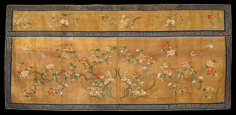 Panel of gold k'ossu with spreading branches of lotus and peonies in the rain field. Above, in a wide band set off from the field by a border of blue k'ossu with Greek Key meander in gold, is a row of flower and fruit sprays. The design is done in shades of red, pink, green and white. Around the edge a the border of the Greek key meander in gold on blue. The panel is in two sections seamed up the middle. Lining of bright pink figured silk. Coarse quality. Note A.P. says this may be late XVIII century.