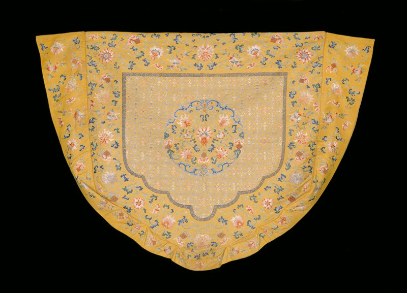 Shaped throne back cover of imperial yellow silk embroidered in a design of lotus, bats, and double peach. The design and the diaper ground of large panel almost identical with that in 42.8.154 and was undoubtedly part of the same set. This cover also has embroidered boxed border. Lining of olive green figured gauze.
