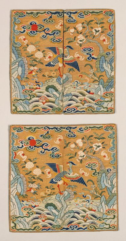 Pair of gold k'ossu mandarin squares. The central motif is a crane? Standing on a rock that emerges from the Eternal Sea. In the field are branches of peach and peony, bats, tight-headed clouds, and the sun. Colors include blue, red, pink, green, and yellow. Some painted details. Lining of blue silk. Inscriptions.