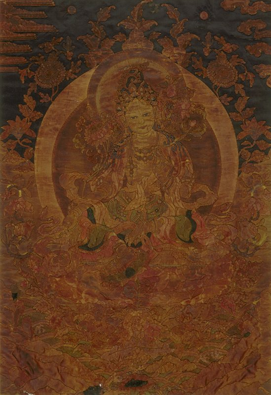 Temple hanging, framed, of satin applique on satin. The design represents Buddha seated on lotus in a field of floral sprays and clouds. The colors, tan, brown, and blue have taken on a prevailing dark rather rusty tone. The Buddha is shown in the gesture of calling the earth to witness.