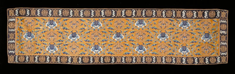 Table cover, embroidered with solid ground of orange silk floss. Design of peony flowers, leaves and bats in satin stitch in shades of blue and green; numerous longevity symbols in couched gold threads. Border of solid black floss ground with bats in blue and longevity symbols in couched gold threads. Lining of blue cotton.