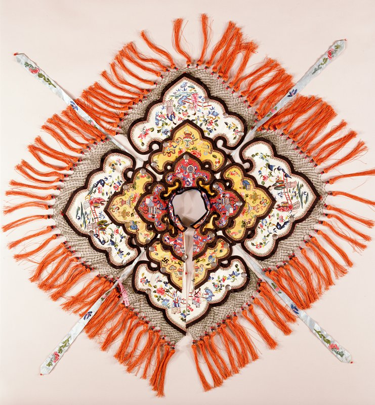 Triple collar, made of many overlapping strips of shaped, embroidered red, white and yellow satin attached to a small standing collar, for a dance costume. The large bottom collar has a tassled fringe border. Small discs of tin are sewn on collars at regular intervals. Lining of cerise silk of floral design.