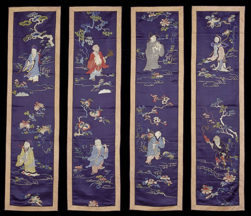 One of a set of four wall handings of embroidered deep blue satin. Each has a design of two of the Eight Immortals. Floral sprays and boughs in the ground. Satin and knot stitch in shades of green, blue, peach, pink, red, yellow and tan. Border of gold and salmon-colored brocade with design of symbols and dragon medallions. Former Classification: Textiles - Tapestry