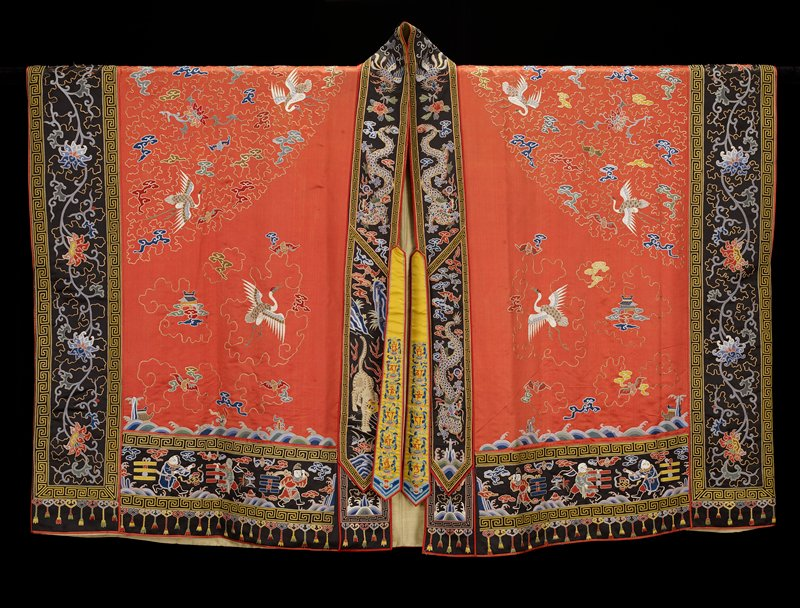 Taoist priest robe of embroidered rust rose satin. On back and shoulders an all-over, loose tendril ground in couched gold threads. On the back conventional Taoist motif, five clawed dragons, bats, cranes, clouds, pagodas in couched gold threads and couched twist in colors. On the front large cranes, bats and clouds. Borders of black satin; collar and front with dragons, bats and clouds; side borders with running lotus and leaf design; bottom border with figures of the Eight Immortals and the Eight Trigrams in couched gold threads, couched twist in colors, satin stitch for faces. Lining of lelmon-yellow silk with medallion pattern.