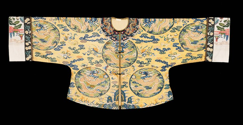 Woman's Short Jacket of pale yellow k'ossu with a design of five-clawed dragon medallions, clouds, bats, narcissus, adn Buddhist symbols in shades of blue, light green, and golden yellow. Along bottom is the Eternal Sea motif, with good luck symbols in the waves. Collar-band of blue k'ossu with five clawed dragons in gild. Cuffs of white k'ossu with a design of figures in a landscape; inner border of black k'ossu with narcissus blossoms -- cuffs later (?). Coat opens down front, and is lined with deep cream silk of medallion design.