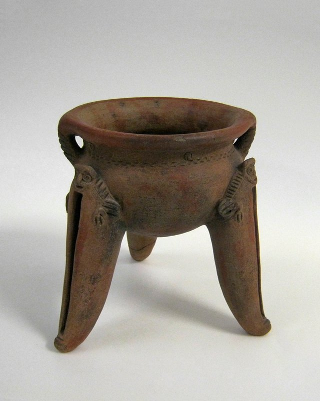 Tripod bowl ornamented with mask and wings of bats at the top of the legs. Legs hollow, with pellets, and slit vertically in front. Two small rigid ring handles with incised lines. Narrow band of incised lines around outer neck.