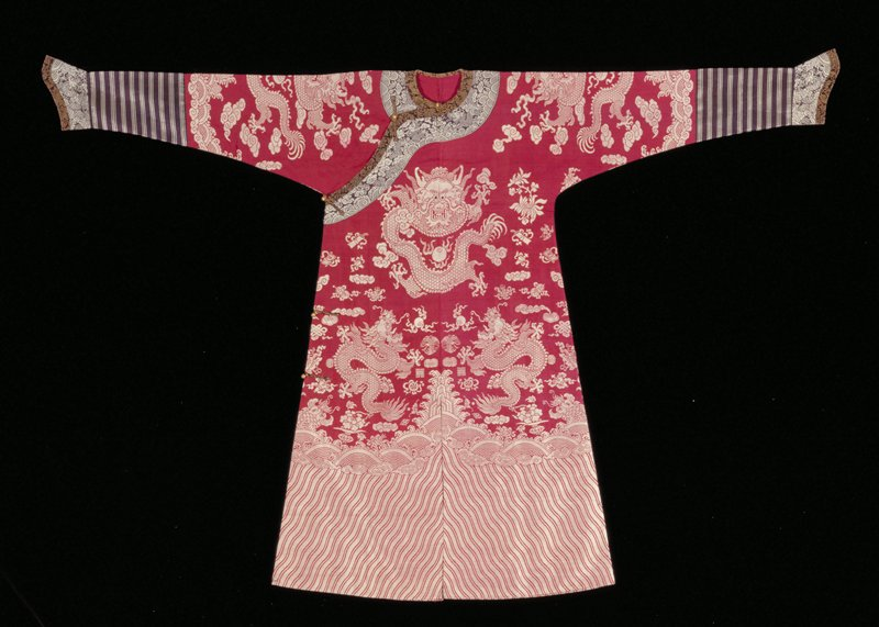 Court Robe of wine-red silk brocade in silvery white. Nine five-clawed dragons. In the field are loosely solid clouds, chrysanthemums, swastikas, Buddhist and Taoist emblems. Conventional border of slightly slanting stripes; single line of snail-like clouds; single line of deep-rolling waves fringed with spray. Below a black border of sleeves a strip of black-blue silk brocaded wtith body designs in silvery white. Edging of black and gold brocade. In body the only departure from red and silver tones are the black spots of the dragon's eyes. Robe unlined but faced.