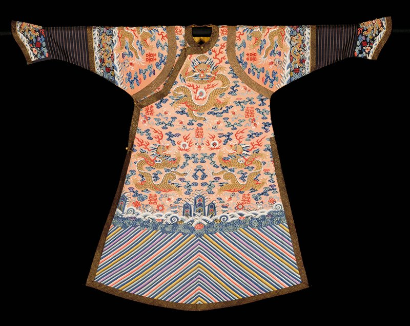 Imperial robe of pale coral-colored k'ossu with nine 5-clawed dragons in gold. Scattered in ground are loose clouds, bats and the double happiness sign in shades of blue, green, red, pink, violet and strong purple. Conventional border with staight slanting stripes; very tight band of small clouds; rolling waves in which appear Buddhist symbols. Olive green in border. Below border on sleeves a strip of fabric striped horozontally. Cuffs and collar band of dark blue k'ossu with the body motifs. Edging of gold and blue fretwork meander, and band of same directly below border of sleves. At arm holes, a wide band of gold and blue brocade of different pattern. Robe slit at sides, lined with yellow damask and faced on all openings with a band of the blue and gold brocade used for the cuff edging. The double happiness character indicates this robe was worn for a wedding. Dragon's eyes embroidered. Some painting.