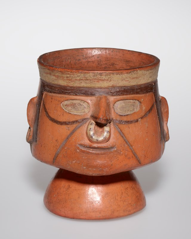 Goblet, portrait head of warrior with ear rings and ring in nose. The face is rather crudely modelled, with painted lines under the eyes and at each side of the mouth. From the valley of Rimac
