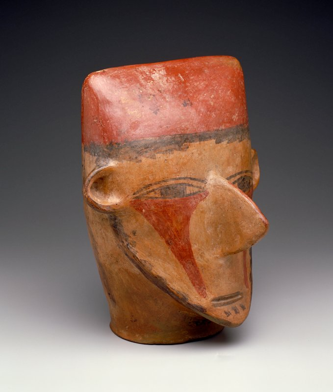 Large head with wide flattened brow and painted face. The enormous, thin nose, ears, and pointed chin are in full relief. The mouth is a narrow slit with black lips; the almond shaped eyes and thin eyebrows are painted. A triangular area, extending from beneath the eyes to the chin on each side of the nose, is painted red. Cheeks edged with black paint, possibly representing a beard. Wavy vertical lines of black on back of skull represent hair, as does the line of black across the forehead. The figure wears a brick red skullcap. Surface highly burnished. The size of this example makes it an important one. Schoeler says: early Nazca--MWS.