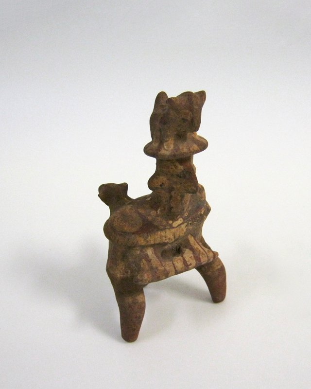 Seated, two-legged figure with tail. Two animal heads in relief project from shoulders in back, and a small animal, possibly a dog, stands astride the brimmed hat worn by the figure. A bar is held out in front of the body in hands that have no form. This bar, possibly a musical instrument, and details of the costume, are painted in red and cream stripes and dots on a reddish pottery ground. Wooden stand. Close to 'Ixtlan del Rio' type.