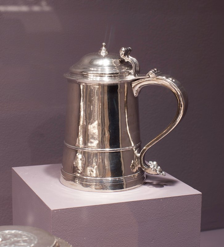tankard, with slender tapered body circled by a moulded band about a third of the way up from a moulded base, domed cover topped by a finial; scroll handle, with an erect scroll thumb piece, terminating in an embossed cherub's head, an applied, moulded drop extends part way down the handle from the hinge, the front of the body is engraved with the monogram EMM