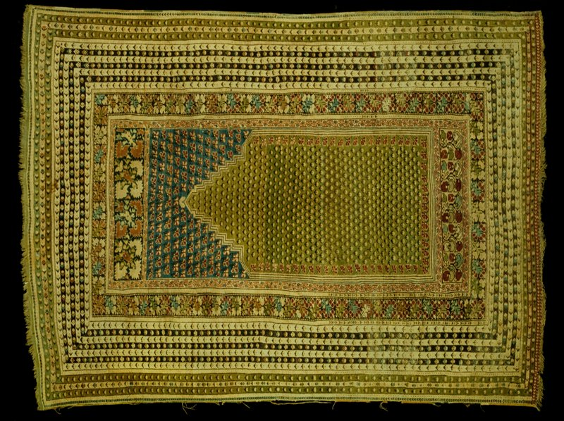 Prayer rug, Kulah. The field of soft green is shaded and filled with rows of conventionalized floral forms and fringed with pinks in profile along the inner border. The field above the prayer niche is soft blue with rows of pink and red blossoms. Above is a wide border of conventionalized pinks in groups of four and below the prayer field another wide border of conventionalized blossoms and leaves in blocks. The main border contains a running band of conventionalized floral sprays. Fourteen narrow borders in pale beige, brown, and green, carry single blossoms and arrowhead motifs. Sides are selvaged, and the upper end has a narrow web ending in short warp fringe. Ghiordes knot, with 12 knots per lineal inch, wool warp and woof. Selvage of one side torn. Many patches.