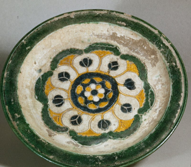Band of green glaze on rim, curled green glaze feet - conventional floral motif. White earthenware, 3 coloured glaze.