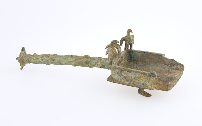 Ceremonial scoop or shovel surmounted by two birds; green patina. Left corner broken off.