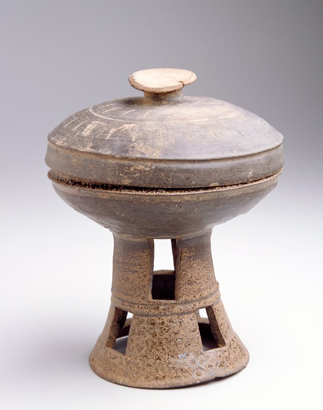 Mounted Cup with domed cover, cup decorated with double row of rectangular perforations, cover has incised line with dots, knob, two bands; gray stoneware, partially overed with brownish ash glaze.